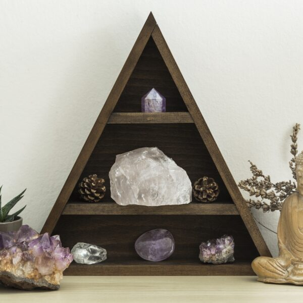 Triangular wooden crystal shelf with succulent plants foliage and wooden statue of Buddha